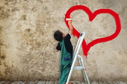 Chłopiec malujący serce na ścianie